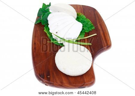 mediterranean cuisine : raw soft feta white cheese round with slices on wooden plate isolated over white background