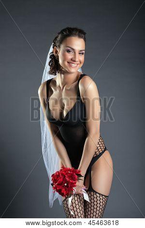 Laughing model posing in black lingerie and veil