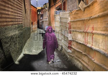 Woman in crimson traditional crimson Moroccan dress walks down narrow street with ocher walls