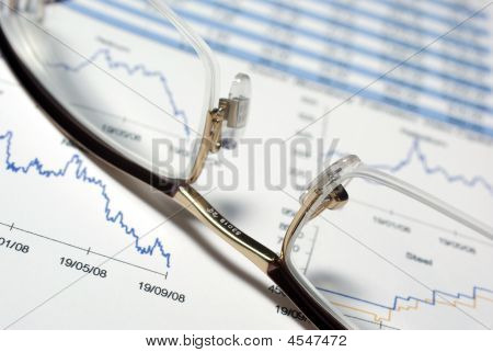 Closeup On Glasses And Financial Report With Charts.