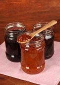 Tasty jam in banks on wooden background