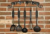 stock photo of kitchen utensils  - Hanging Kitchen utensils on a brick wall for use in cooking or baking - JPG