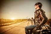 stock photo of rebel  - Biker girl in a leather jacket on a motorcycle looking at the sunset - JPG