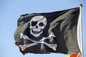 picture of skull crossbones flag  - pirate flag flying against a blue sky - JPG