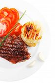 meat savory : grilled beef fillet served on white plate with tomatoes and potatoes isolated over whi