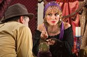 stock photo of gypsy  - Pretty gypsy lady pointing with finger over crystal ball - JPG