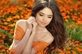 stock photo of marigold  - Young woman outdoors portrait over orange marigold flowers - JPG