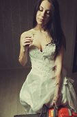 picture of gory  - Pretty bride with chamomile and chainsaw stands in empty room - JPG
