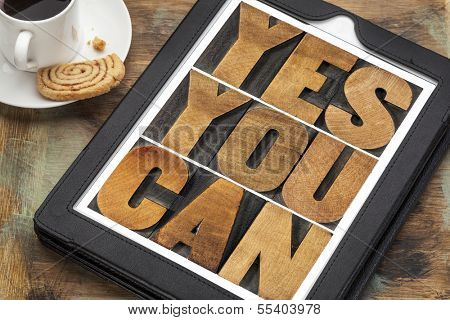 Yes you can - motivational slogan on a digital tablet with a cup of coffee