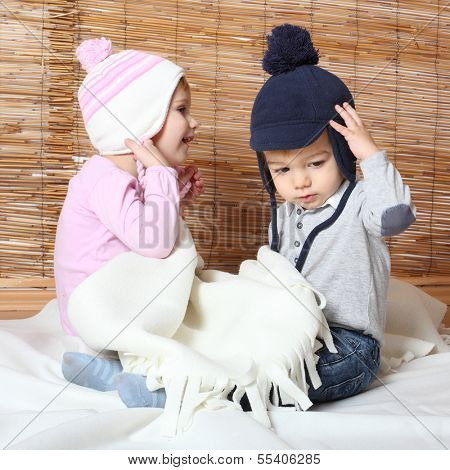 Little kids dressed in warm knitwear for cold weather.
