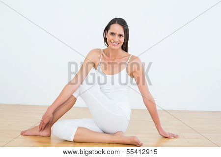 Portrait of a fit young woman doing the half spinal twist pose in fitness studio