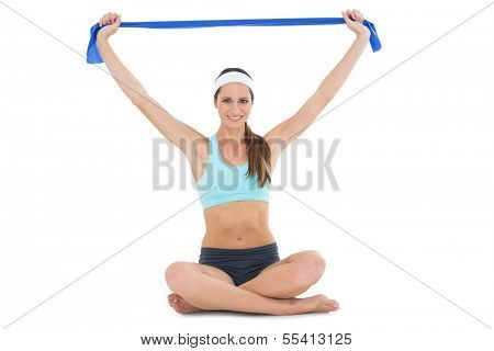 Full length portrait of a fit young woman exercising with a blue yoga belt over white background