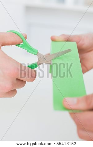 Extreme close-up of hands holding kinesio tape and scissors over white background