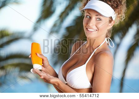 Sunscreen woman. Girl putting sun block on beach holding orange sun tan lotion bottle.