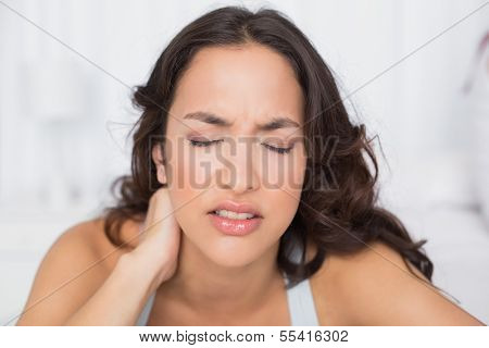 Close-up of a beautiful young woman suffering from neck pain with eyes closed at home