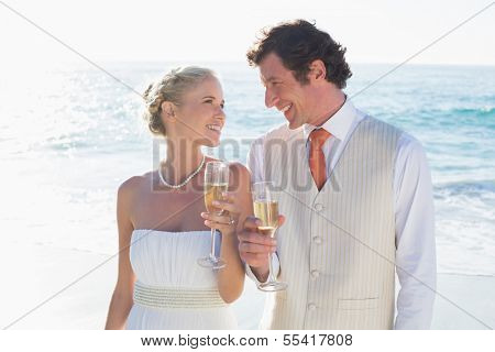 Young newlyweds toasting with champagne smiling at each other at the beach