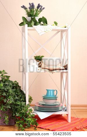 Beautiful white shelves with tableware and decor, on color wall background