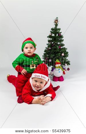 Two Baby Boys Dressed As Santa Claus And Santa's Helper Lying Next To Christmas Tree.