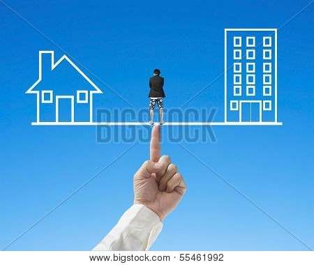 Thoughful Man Standing On Seesaw With Office And Home