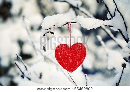 Textile heart hanged on a snow-covered forest bush