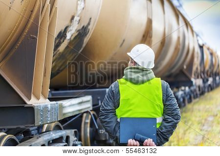 Railroad employee with folder near the tank wagons