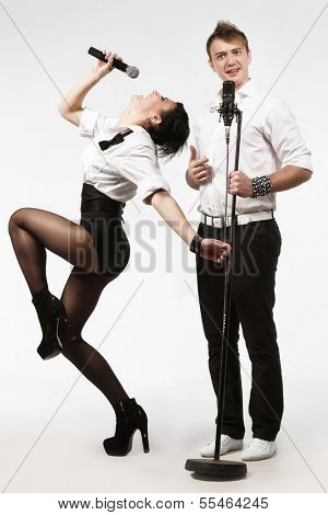 Couple performs duet singing microphone over white