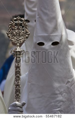 Penitent with staff of silver during a procession of holy week