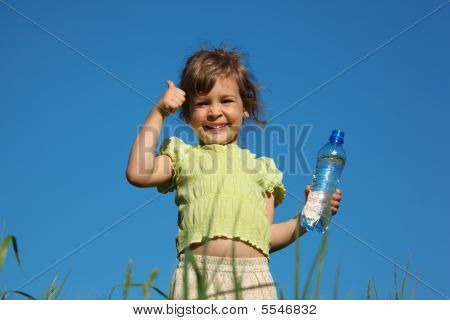 Girl In Grass With Plastic Bottle With Water Shows Gesture