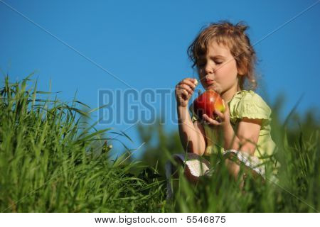 Girl Eats Red Apple In Grass Against Blue Sky