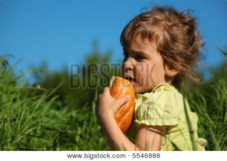 Girl Eats Bread In Grass Against Blue Sky