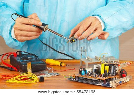 Serviceman solder electronic components of device in service workshop