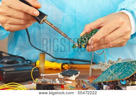 Repair electronic board of device with a soldering iron in service workshop