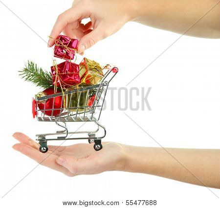 Hand holding Christmas gifts in shopping trolley, isolated on white