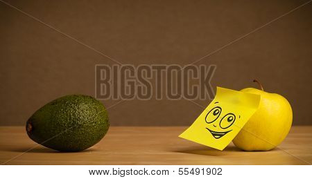 Apple with sticky note reacting to avocado