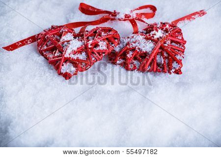 Two beautiful romantic vintage red hearts tied together with a ribbon on a white snow background. Love and St. Valentines Day concept.