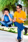 Chinese Asian father talking to his son but will not listening, refusing the good advice