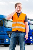 Logistics - proud driver or forwarder with mobile phone in front of trucks and trailers, on a transs