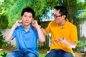 stock photo of not talking  - Chinese Asian father talking to his son but he will not listening - JPG