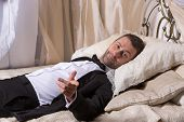 stock photo of recliner  - Elegant handsome playboy in a bow tie and suit reclining on a bed in an elaborate bedroom with a seductive smile on his face - JPG