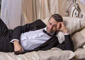 Постер, плакат: Elegant Playboy Reclining On A Bed