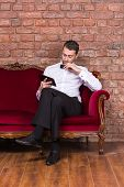 picture of settee  - Conceptual image of an elegant businessman lying relaxing on a settee against a brick wall and reading tablet - JPG