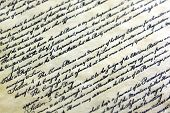 stock photo of scribes  - Old grunge paper with elegant handwriting on black background - JPG