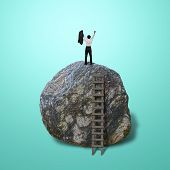stock photo of retarded  - Cheered businessman climb on top of large rock in green background - JPG