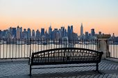 Bench in park and New York City midtown Manhattan at sunset with skyline panorama view over Hudson R