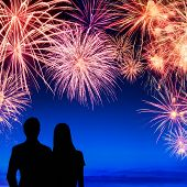 image of firework display  - Spectacular fireworks display on deep blue sky with silhouettes of a young couple watching it - JPG