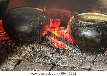 Cooking traditional meal in hearth furnace