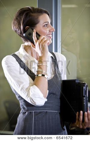 Young woman on mobile phone standing by glass door