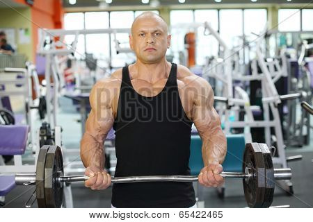 Strong bodybuilder in black jersey raises big heavy barbell in gym hall