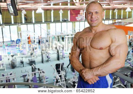 Smiling shirtless sunburnt bodybuilder stands in big modern gym hall