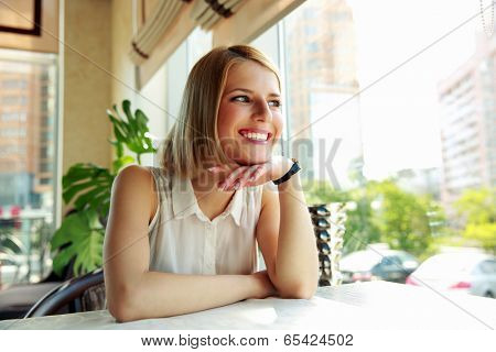 Young cheerful woman sitting in cafe and looking at window